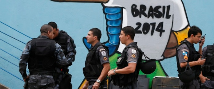 Riot police gather in front of a mural of the mascot for the 2014 World Cup soccer tournament, called Fuleco, near the Maracana stadium ahead of the Confederations Cup soccer final between Brazil and Spain in Rio de Janeiro, Brazil, Sunday, June 30, 2013. (Source: AP Photo/Victor R. Caivano)